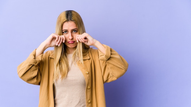 Giovane donna caucasica bionda che si lamenta e piange sconsolato.