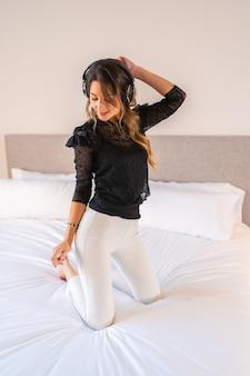 Giovane donna caucasica bionda con le cuffie che balla e si gode la musica sopra il letto a casa
