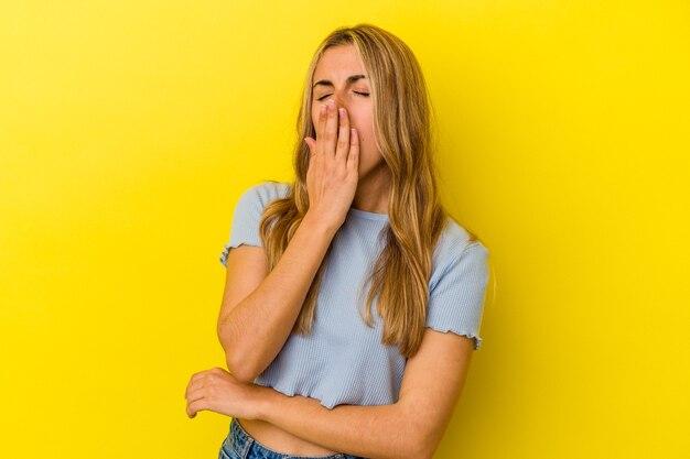 Giovane donna caucasica bionda che sbadiglia mostrando un gesto stanco che copre la bocca con la mano.