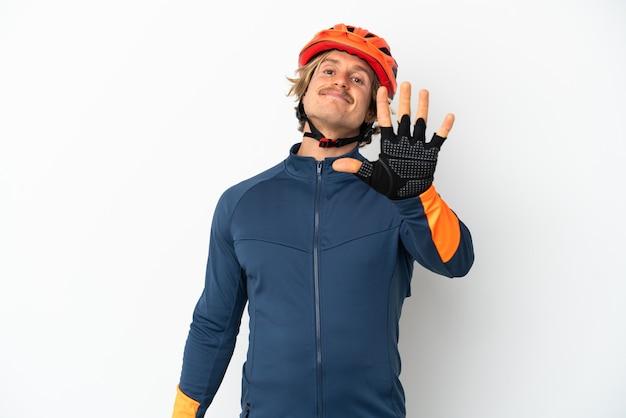 Uomo giovane ciclista biondo isolato sul muro bianco contando cinque con le dita