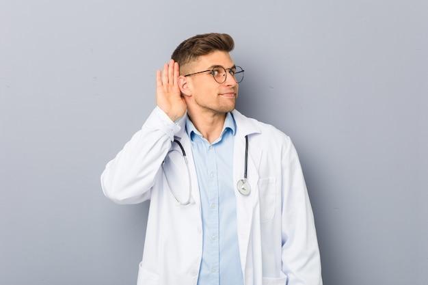 Giovane uomo biondo del medico che prova ad ascoltare un gossip.