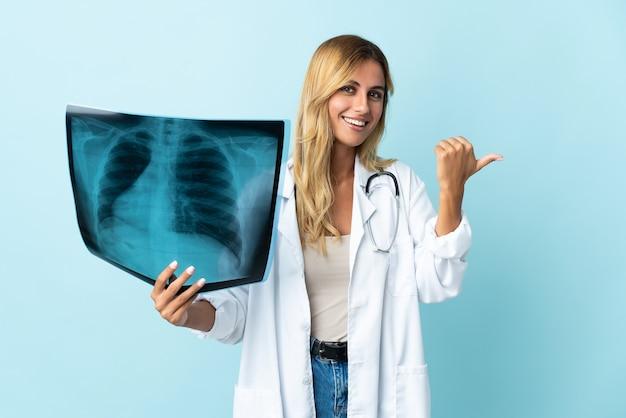 Giovane donna bionda medico isolata che punta al lato per presentare un prodotto