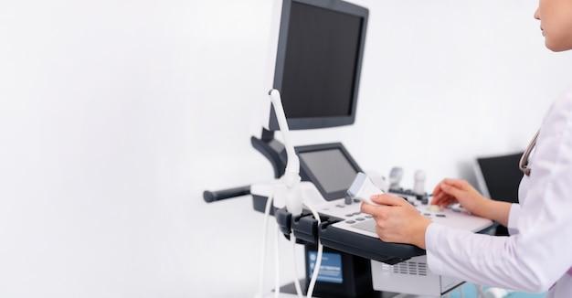 Giovane medico biondo che lavora alla macchina di ultrasuono in nuova clinica. concetto di assistenza sanitaria