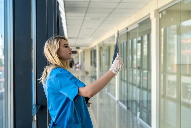 Giovane medico femminile biondo che porta l'uniforme blu con lo stetoscopio che tiene la pellicola dei raggi x del torace e che controlla sulla polmonite. covid19