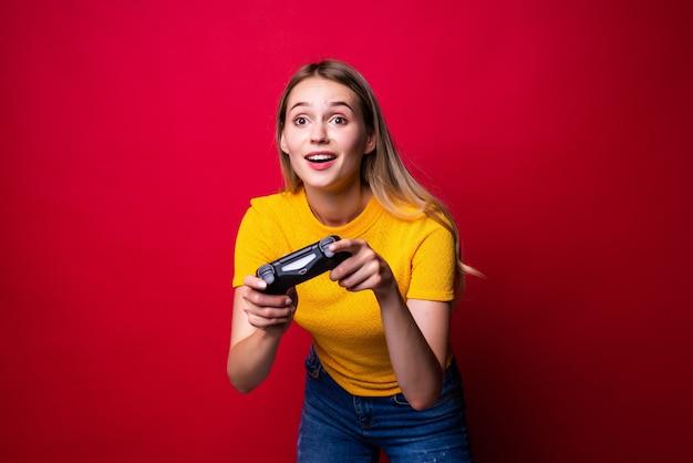 Giovane donna bionda del giocatore utilizzando il gamepad per giocare ai videogiochi isolati sopra la parete rossa