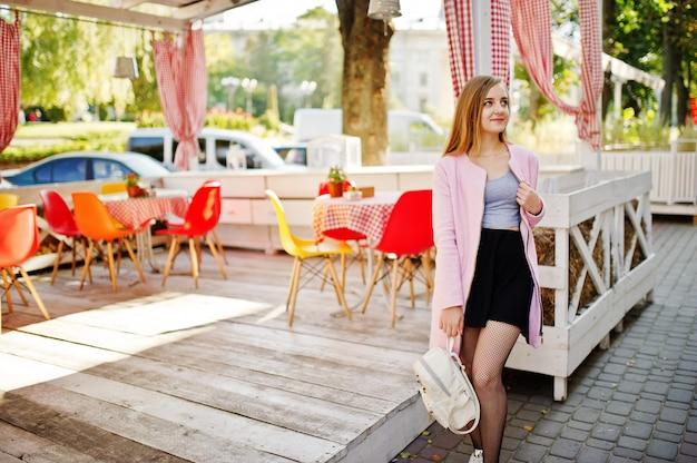 La giovane ragazza bionda in gonna nera e cappotto rosa con lo zaino della donna ha posato contro il ristorante del terrazzo dell'estate all'aperto.