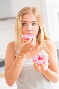 La giovane ragazza bionda mangia le ciambelle rosa nella cucina di casa con emozioni di gusto.
