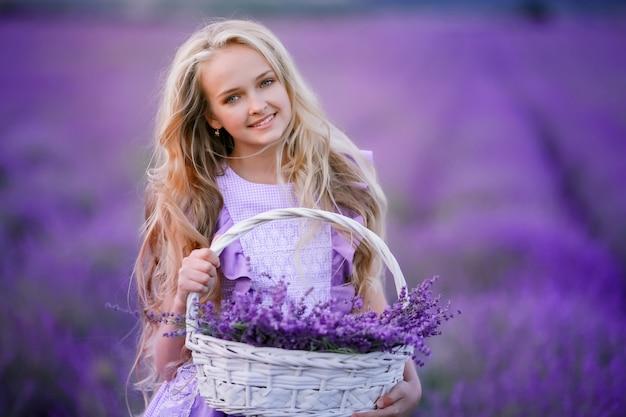 Giovane ragazza bionda in un campo con lavanda che tiene un cestino in sue mani