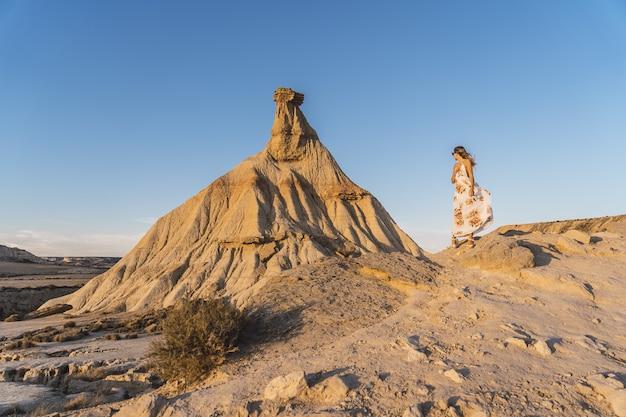 Giovane ragazza bionda in abiti graziosi vicino a una scogliera in un deserto a las bardenas reales, navarra, spagna