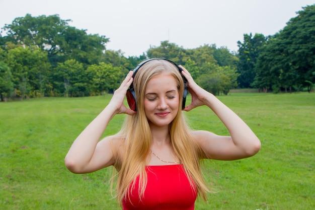 Giovane ragazza bionda sorridente felice utilizzando le cuffie al parco.