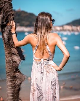 Giovane ragazza bionda in occhiali da sole in posa vicino all'albero in una spiaggia di san sebastian, spain