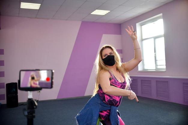 Una giovane ragazza bionda indossa una maschera nera durante una pandemia conduce sessioni di allenamento in un club sportivo.