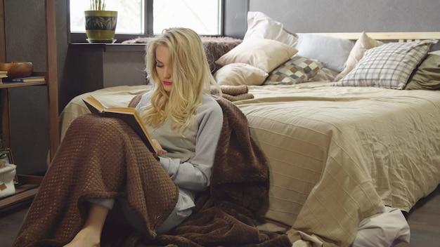 La giovane bionda è seduta sul pavimento in una coperta accanto al letto e sta leggendo un libro.