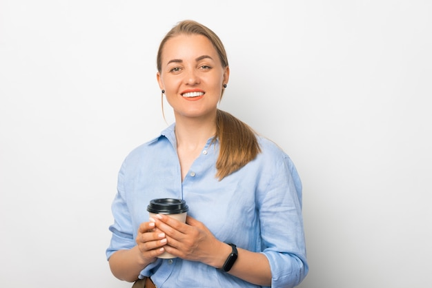 La giovane signora bionda che sorride alla macchina fotografica sta tenendo una tazza di caffè da asporto.