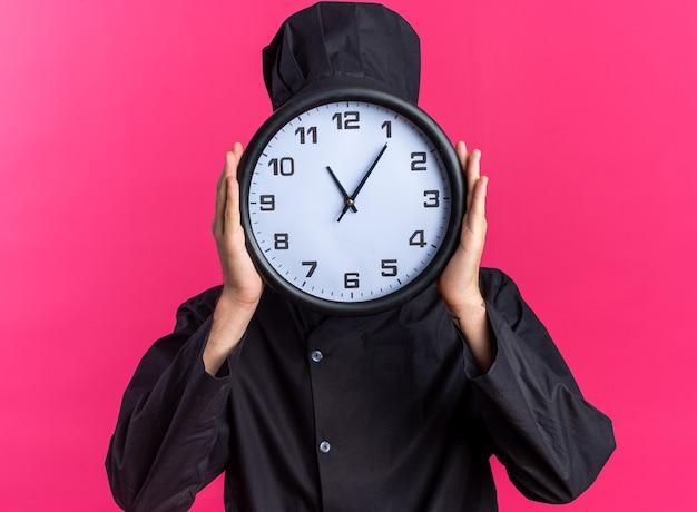 Giovane cuoco maschio biondo in uniforme da chef e berretto che tiene l'orologio davanti al viso isolato su parete rosa
