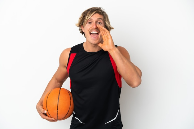 Giovane uomo biondo che tiene una palla di pallacanestro isolata sul muro bianco che grida con la bocca spalancata