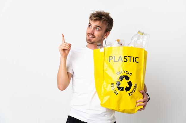 Giovane uomo biondo che tiene un sacchetto di riciclaggio pieno di carta da riciclare isolato su sfondo bianco rivolto verso l'alto una grande idea