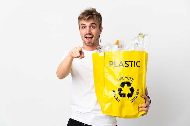 Giovane uomo biondo che tiene un sacchetto di riciclaggio pieno di carta da riciclare isolato