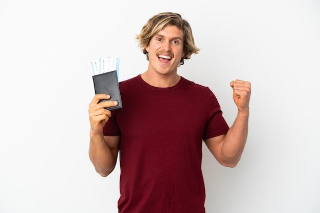 Giovane uomo biondo isolato su sfondo bianco felice in vacanza con passaporto e biglietti aerei
