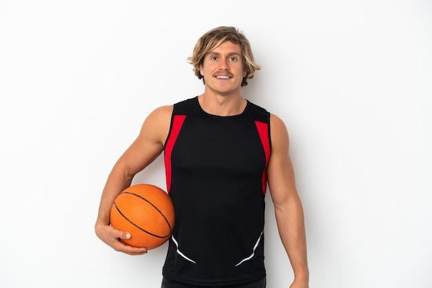 Giovane uomo biondo isolato su sfondo bianco giocando a basket
