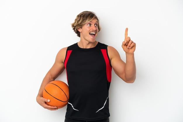Giovane uomo biondo isolato sul muro bianco, giocare a basket e avere un'idea