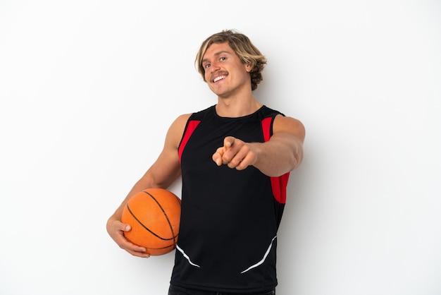 Giovane uomo biondo isolato sul muro bianco, giocando a basket e indicando la parte anteriore
