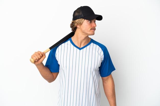 Giovane uomo biondo che gioca a baseball isolato su sfondo bianco guardando al lato