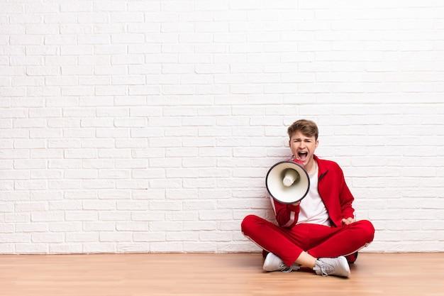 Giovane uomo biondo che si siede sul pavimento con un megafono