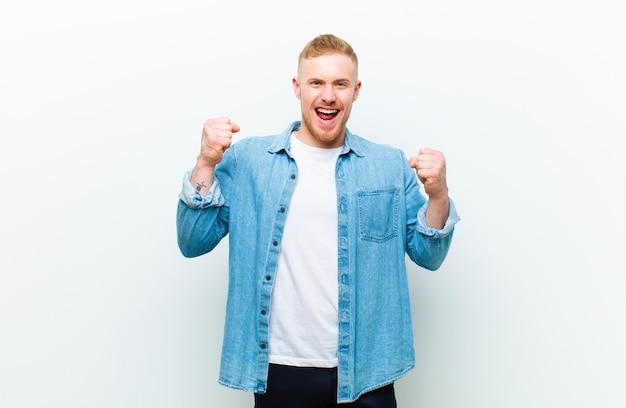 Camicia d'uso dei jeans del giovane uomo biondo che grida aggressivamente con un'espressione arrabbiata o con i pugni serrati che celebra successo su bianco