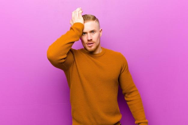 Giovane uomo biondo che indossa un maglione che solleva il palmo sulla fronte pensando oops, dopo aver fatto uno stupido errore o aver ricordato, sentendosi stupido