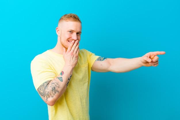 Giovane uomo biondo che indossa maglietta gialla sentirsi felice, scioccato e sorpreso, coprendo la bocca con la mano e indicando lo spazio laterale della copia