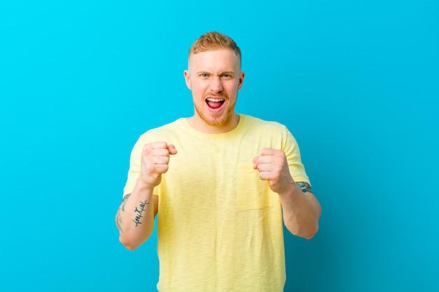 Giovane uomo biondo che indossa una maglietta gialla che grida in modo aggressivo con sguardo infastidito, frustrato, arrabbiato e pugni stretti, sentendosi furioso