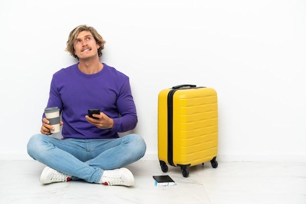 Giovane uomo biondo con la valigia che si siede sul pavimento che tiene il caffè da portare via e un cellulare mentre pensa a qualcosa