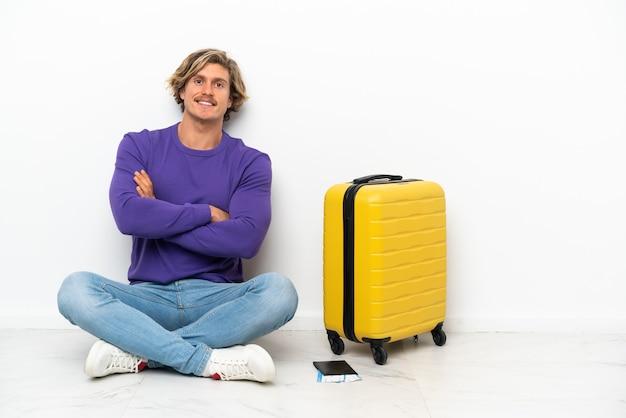 Giovane uomo biondo con la valigia che si siede sul pavimento mantenendo le braccia incrociate in posizione frontale