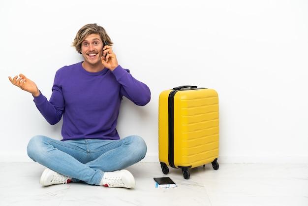 Giovane uomo biondo con la valigia che si siede sul pavimento mantenendo una conversazione con il telefono cellulare con qualcuno