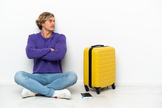 Giovane uomo biondo con la valigia che si siede sul pavimento in posizione laterale