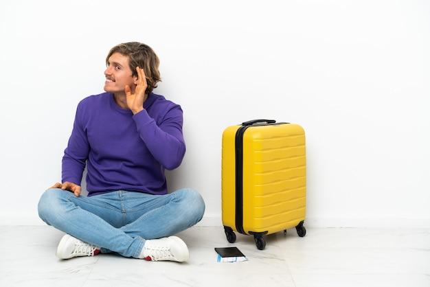 Giovane uomo biondo con la valigia che si siede sul pavimento ascoltando qualcosa mettendo la mano sull'orecchio