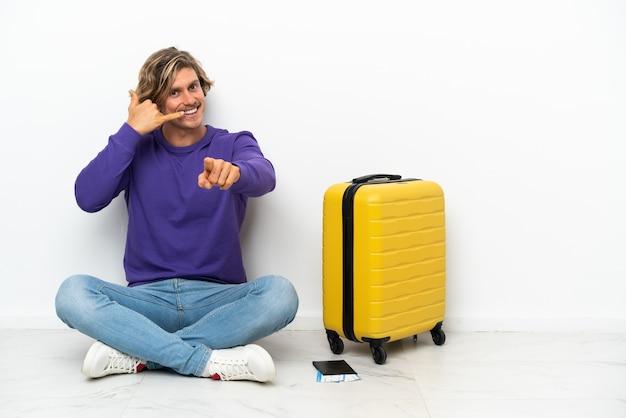 Giovane uomo biondo con la valigia che si siede sul pavimento che fa telefono
