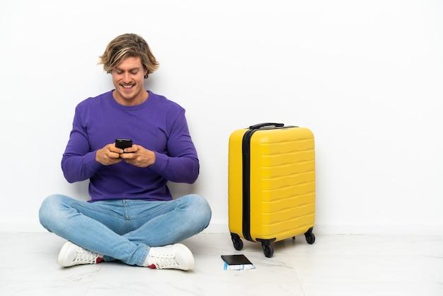Giovane uomo biondo con la valigia che si siede sul pavimento inviando un messaggio con il cellulare