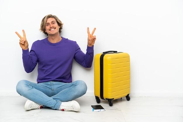 Giovane uomo biondo con la valigia che si siede sul pavimento che mostra il segno di vittoria con entrambe le mani