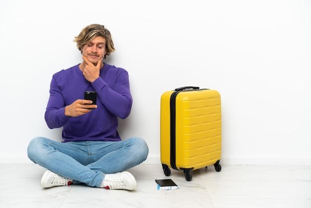 Giovane uomo biondo con la valigia che si siede sul pavimento pensando e inviando un messaggio