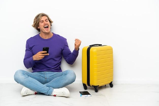 Giovane uomo biondo con la valigia che si siede sul pavimento con il telefono in posizione di vittoria