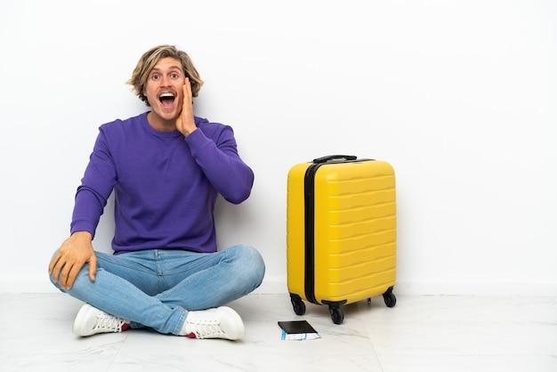 Giovane uomo biondo con la valigia che si siede sul pavimento con espressione facciale sorpresa e scioccata