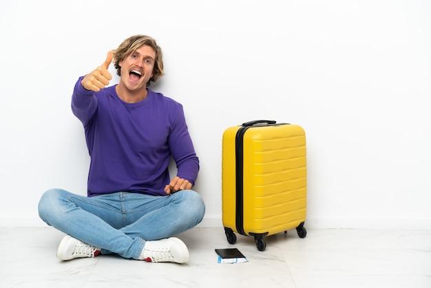 Il giovane uomo biondo con la valigia che si siede sul pavimento con i pollici in su è successo