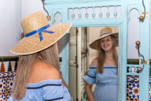 Giovane donna incinta bionda in un vestito blu che prova un cappello davanti a uno specchio.