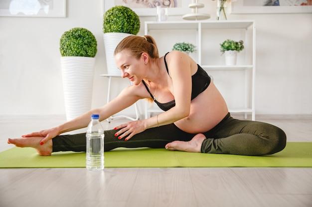 Giovane donna incinta bionda che fa sport a casa sulla stuoia. foto di alta qualità