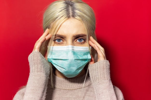 Giovane ragazza bionda malata con gli occhi azzurri, tenendo la mano sulla bocca, indossando maschera antinfluenzale medica, isolata sulla parete rossa.