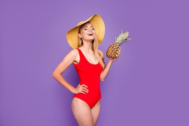 Giovane ragazza sorridente bionda che indossa costume da bagno rosso e cappellino da sole che tiene mela di pino