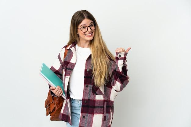 Giovane donna bionda studentessa isolata che punta al lato per presentare un prodotto