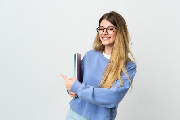 Donna giovane studentessa bionda isolata sul muro bianco che punta indietro
